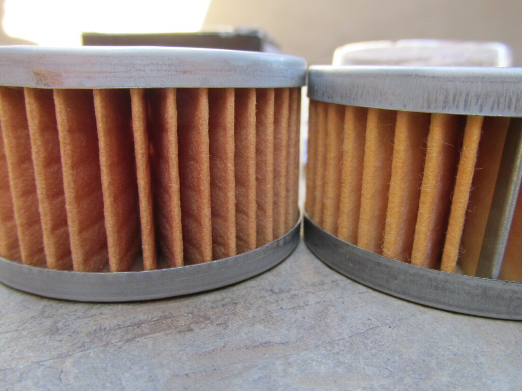 Tusk filter on left: measures 33.94 mm in overall height; Suzuki filter on right: measures 32.34 mm in overall height. In my experience, the greater overall height of the Tusk filter directly causes the small O-ring to be displaced, greatly compromising the seal.