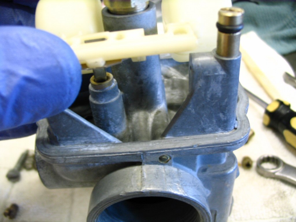 Insert the float needle into the carburetor body and position the float between the hinges.