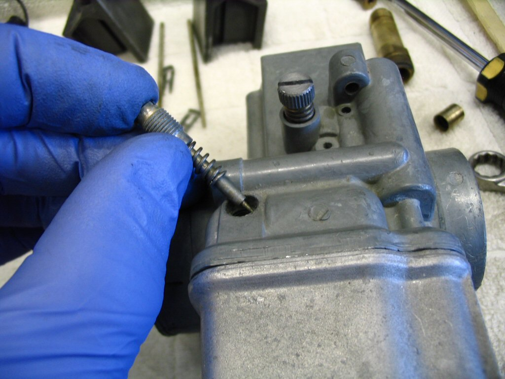 Insert the mixture speed screw and spring into the body of the carburetor. Screw it in until it bottoms out. DO NOT OVERTIGHTEN! Just bottom it out gently. Then, back it out the number of turns specified by the workshop manual (generally 1 1⁄2 - 2 turns for the left carburetor and 1 3⁄4 - 2 1⁄4 turns for the right carb).