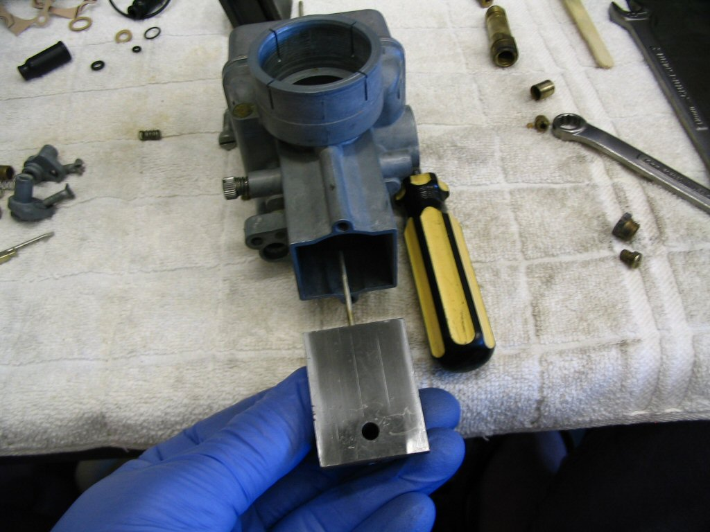 Insert the slide complete with tapered needle into the body of the carburetor. Notice that the large flat area of the slide must face the intake manifold, not the air filter.