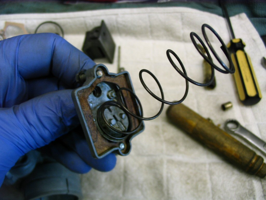 Insert the bent end into the carburetor top. This holds the spring in place.