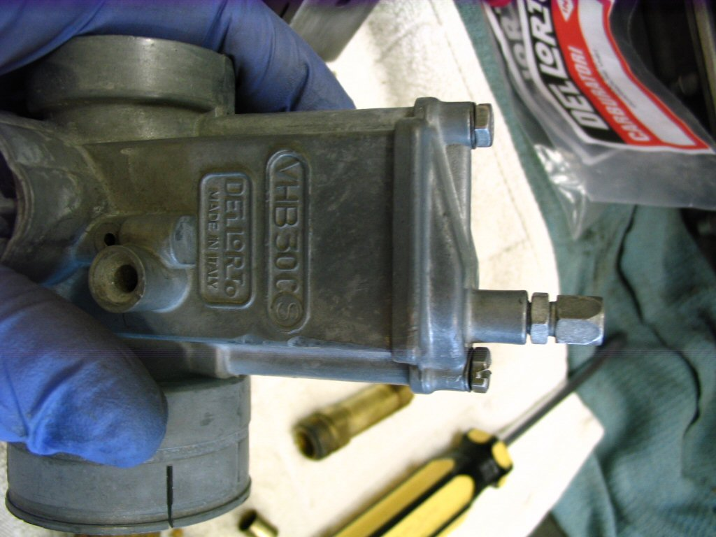 Hold the top down on top of the carburetor body and screw the top in place. DO NOT OVERTIGHTEN THESE BOLTS! They only take a light snug and are far too easy to strip. Be careful. I will also reemphasize, hold the top in its finished position and then screw the bolts in place. That is, don't use the bolts to pull the top into position.