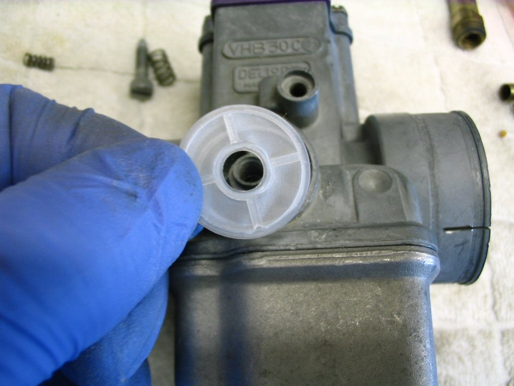 Fit a new plastic fuel filter to the carburetor fuel inlet. Note: the filters do not come with the carburetor kit and must be ordered separately.