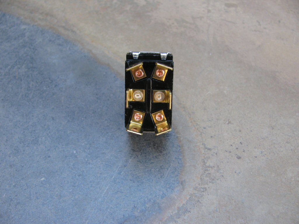 The terminals on the bottom of the toggle switch.