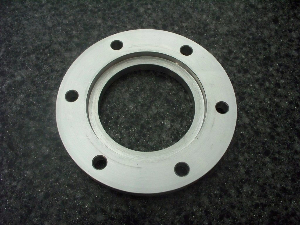 Disc brake spacer as used to fit a disc brake to drum brake Moto Guzzi V700, V7 Special, Ambassador, 850 GT, 850 GT California, Eldorado, and 850 California Police motorcycles.Spacer made by Joe Kenny.