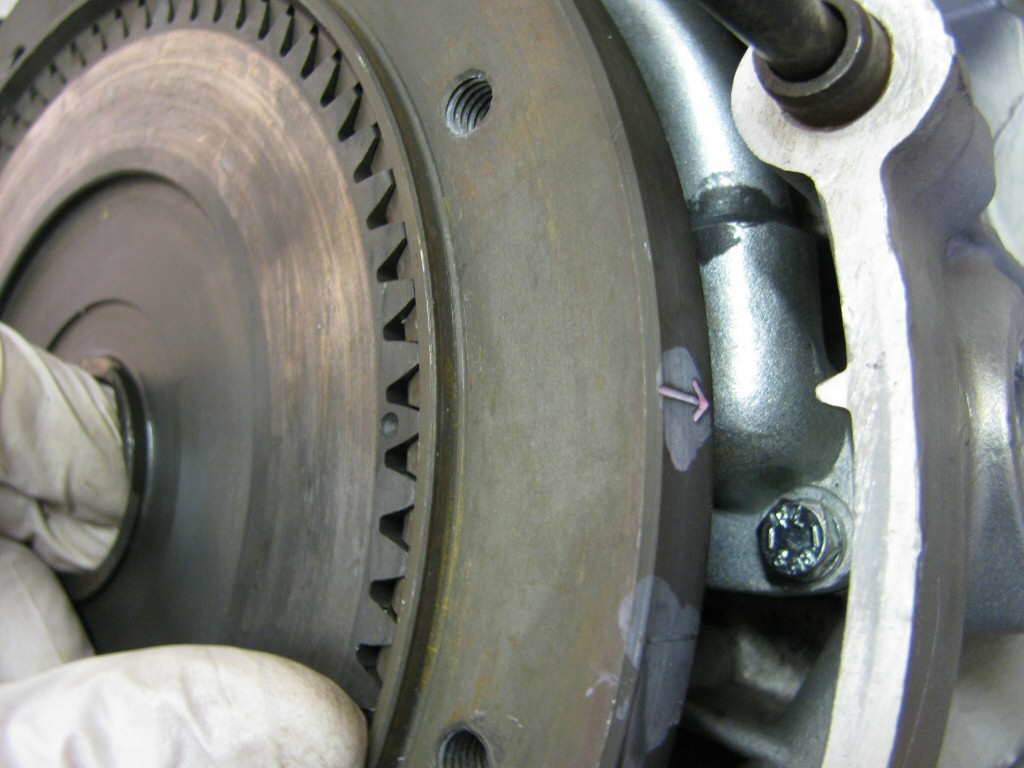 Fit the pressure plate. Note that the dot on the tooth must align with the arrow on the flywheel. Doing so is necessary to make sure the springs fit into the approprieate recess.