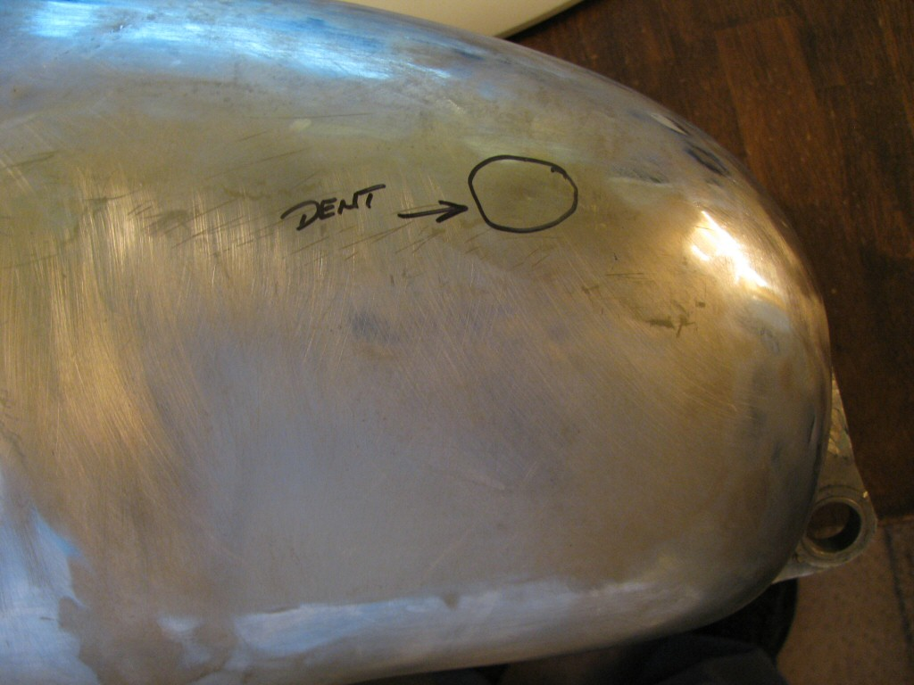 Small dent in the left chrome panel area of the tank.