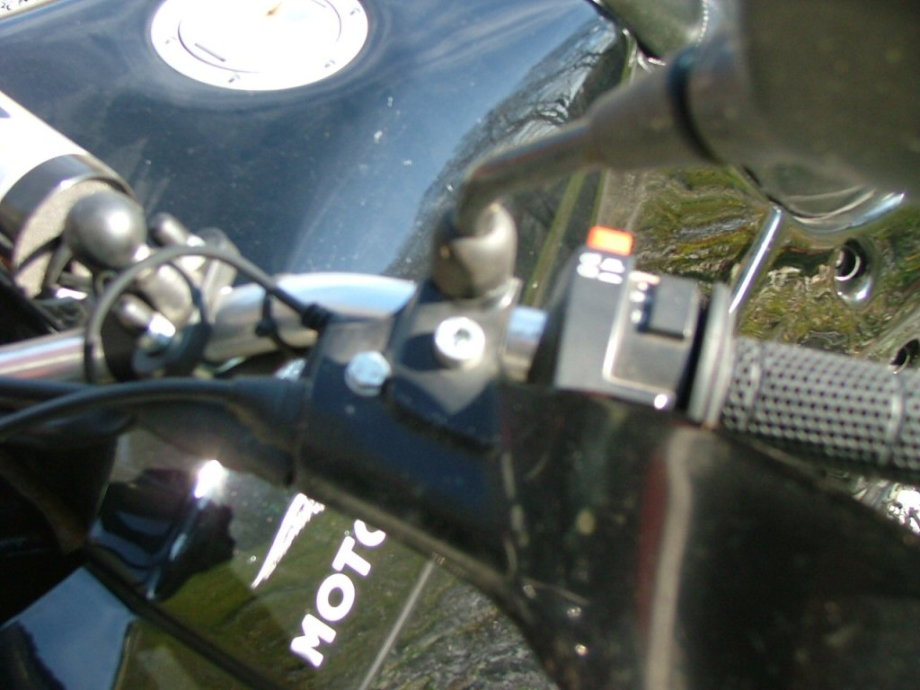Close-up of left guard sculpted for relief around mirror stalk, extra hole drilled inboard of lever pivot bolt to stabilize mount, bolt goes through unused factory hole. Close sculpting of mirror mount cutout helps with stability also. Slight trimming of rubber cable boots is necessary also. Becomes obvious as you progress. Mounting Triumph Tiger hand guards on a Moto Guzzi Quota 1100 ES.