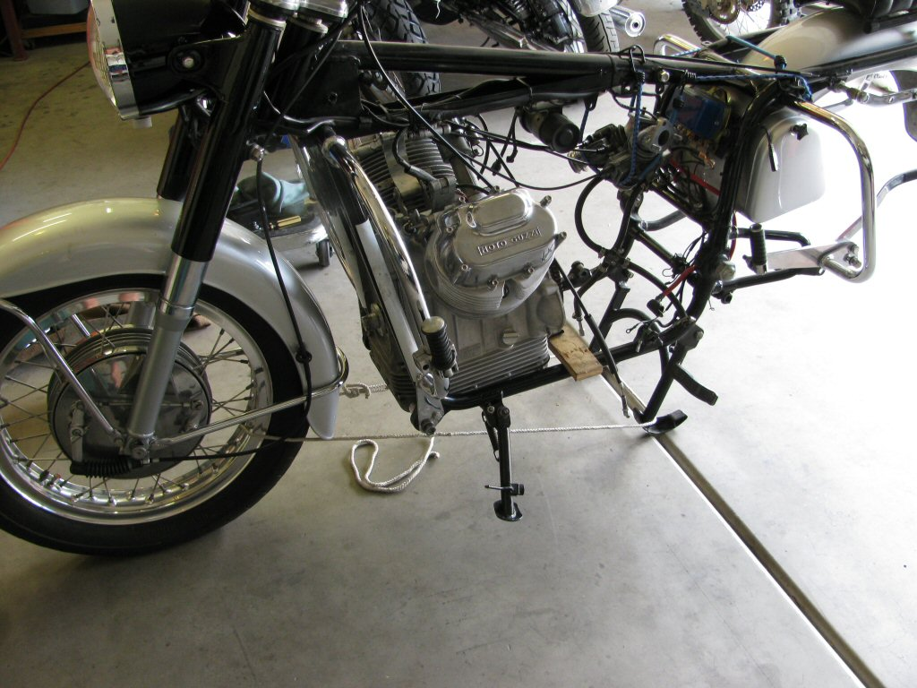 Front engine mounting bolt in place. Center stand prevented from retracting by a length of rope tied around the front wheel.