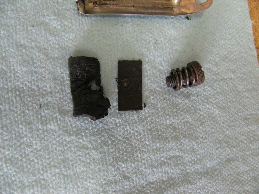 Rubber friction material (left), thin metal backing plate for the friction material (so the screw does not push through the rubber friction material), friction screw and spring.