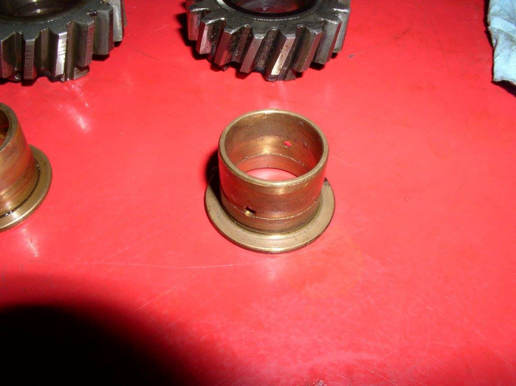 The early bushing has a shallow groove inside and out with two radial holes.