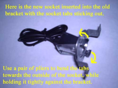 Here is the new socket inserted into the old bracket with the socket tabs sticking out. Use a pair of pliers to bend the tabs towards the outside of the socket, while holding it tightly against the bracket.