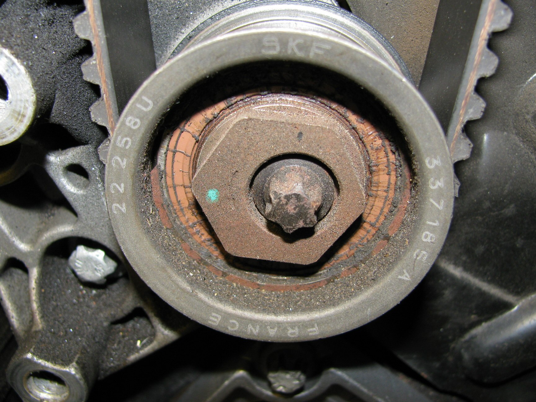 Upper idler pulley. Note the location of the green dot indicating a good initial position of 9 o'clock.