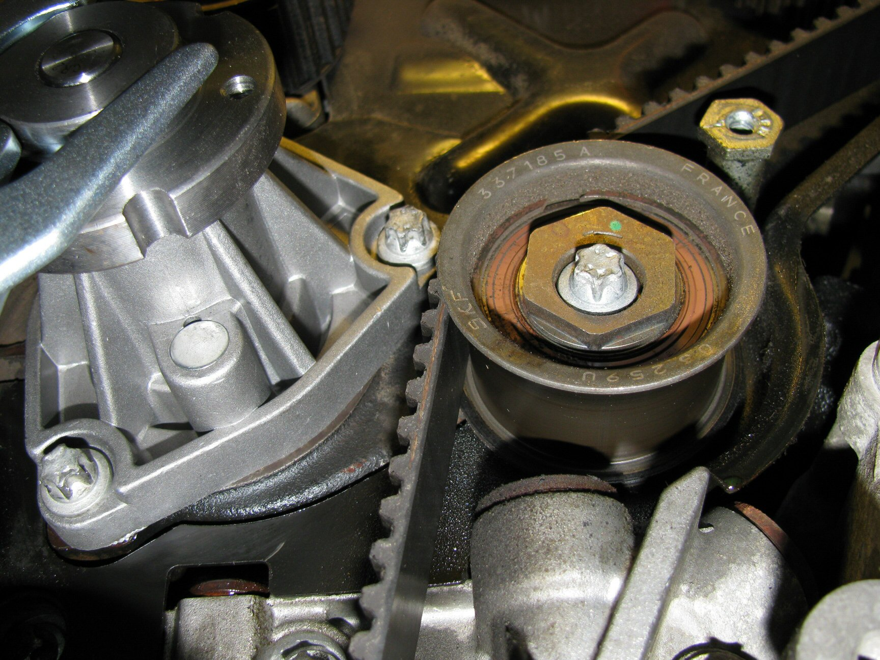 Lower idler pulley. Note the location of the green dot indicating a good initial position of 12 o'clock.